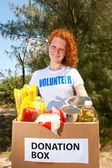 Volunteer carrying food donation box — Stock Photo