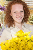 Woman holding a bunch of yellow flowers — Stock Photo
