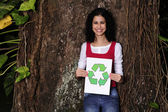Recycling: woman in the forest holding a recycle sign — Stock Photo