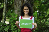 Environment conservation: woman in the forest holding a go green sign — Stock Photo