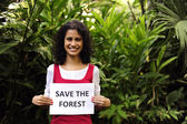 Environment conservation: woman holding a save the forest sign — Stock Photo