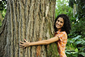 In love with nature: woman hugging a tree in the forest — Stock Photo