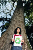 Recycling: woman in front of a tree holding a recycle sign — Stock Photo