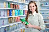 женщина в аптеке, покупая шампунь — Стоковое фото