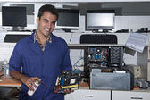 Computer technician with motherboard at workshop — Stock Photo