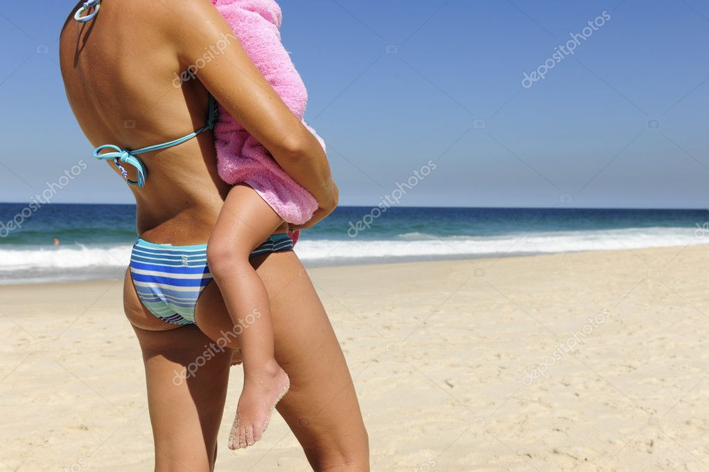 Summer vacation on the beach: mother carrying her daughter  Stock Photo #10955548