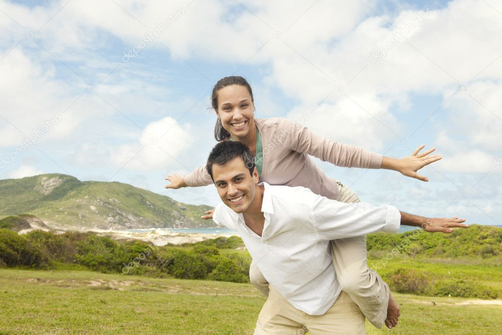 Happy hispanic couple in love, man giving piggyback to woman — Stock Photo #10959746