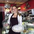 Small business: waitress showing a tasty cake — Stock Photo