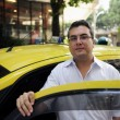 Stock Photo: Portrait of taxi driver with cab