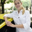 Portrait of a female taxi driver with her new cab — Stock Photo #10960787
