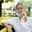 Portrait of a female taxi driver with her new cab — Stock Photo