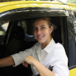 Portrait of a female taxi driver driving her new cab — Stock Photo