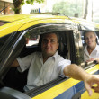Taxi driver showing passenger a landmark — Stock Photo
