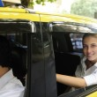 Happy female passenger inside of a taxi - Stock Photo