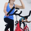Stock Photo: Woman cycling at the gym