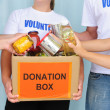 Volunteers putting food in donation box — Stock Photo #10961857