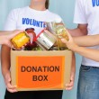 Volunteers putting food in donation box — Foto de stock #10961933