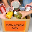 Volunteers putting food in donation box — ストック写真