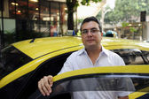 Portrait of a taxi driver with cab — Stock Photo