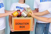 Volunteers putting food in donation box — Stock Photo