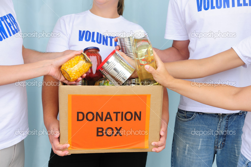 Volunteer putting food in a donation box   #10961857