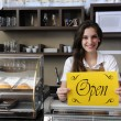 Happy owner of cafe showing open sign — Stock Photo #11217647