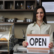 Happy owner of a cafe showing open sign — Stock Photo