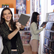 Happy women at the video rental store - Stok fotoğraf