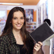 Happy woman at the video rental store — Stock Photo