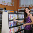 Teenage girl at the video rental store — Stock Photo #11217705