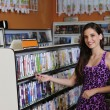 Teenage girl at the video rental store — Stock fotografie