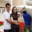 Moving home: Couple infront of new house — Stock Photo