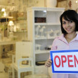 Small business owner: woman holding an open sign — Zdjęcie stockowe
