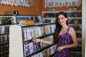 Teenage girl at the video rental store — Stock Photo