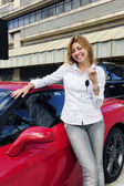Woman showing key of new red sports car — Stock Photo