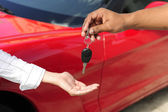Woman receiving car key from salesman — Stock Photo