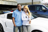 Multiethnic couple buying a new car — Stock Photo