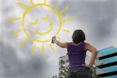 Woman painting the sun onto the cloudy sky — Stock Photo