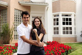 Happy homeowners infront of new house — Stock Photo