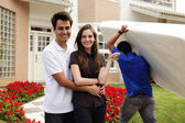 Moving home: Couple infront of new house — Stockfoto