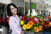Woman with huge bouquet of flowers outdoors — Stock Photo
