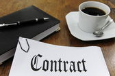 Contract and coffee on a desk — Stock Photo