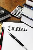 Contrato e calculadora sobre a mesa — Foto Stock