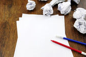 Brainstorming: empty paper on desk with many paperballs — Stock Photo