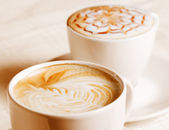 Coffee cup with artistic cream decoration — Stock Photo