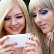 Royalty-Free Stock Photo: Two girl friends using a smartphone