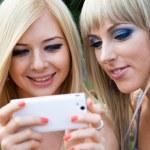 två väninnor med hjälp av en smartphone — Stockfoto