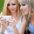 Two girl friends using a smartphone — ストック写真