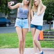 Foto Stock: Two beautiful young girl friends with a photo camera