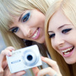 Two beautiful young girl friends with a photo camera — Foto de Stock